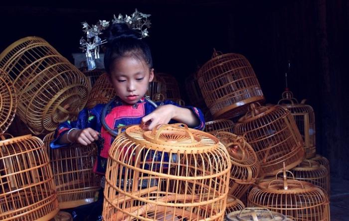 Девочка помогает родителям изготавливать птичьи клетки.