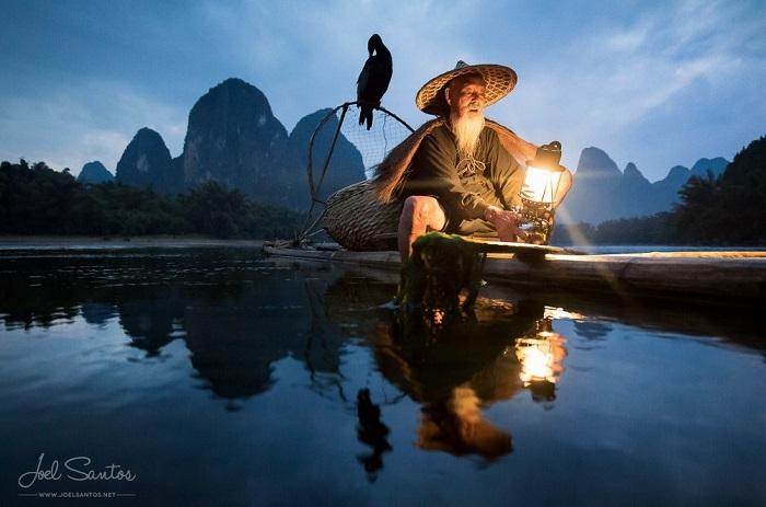Китайский рыбак, на рыбалке на горном озере, в узком бревенчатом плоту, с корзиной для рыбного улова и сидящим бакланом.