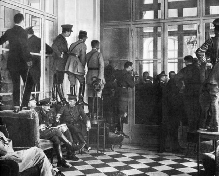 Люди стоят на кушетках, столах и стульях, чтобы увидеть подписание Версальского договора, официально завершившего Первую мировую войну. 28 июня 1919 года.
