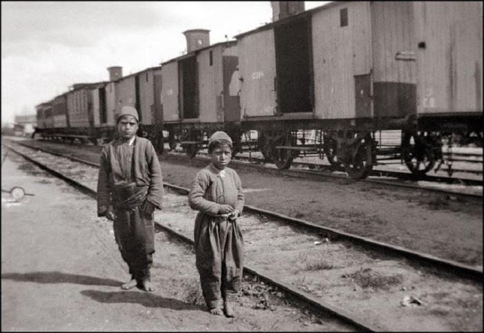 Подростки из малообеспеченной семьи прогуливаются по железной дороге.