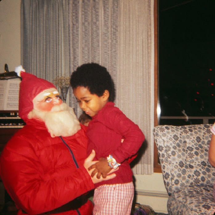 Застенчивый ребенок пытается убежать от Санта-Клауса.