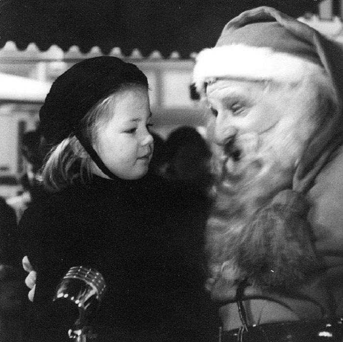 Девочка и Санта в канун Рождества поют рождественские песни.