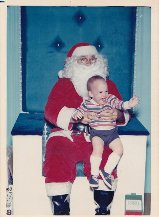 Санта-Клаус удерживает плачущего ребенка, который вырывается из его рук прямо к маме.