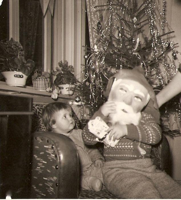 Брат, одевши маску Санты, пугает младшую сестренку.