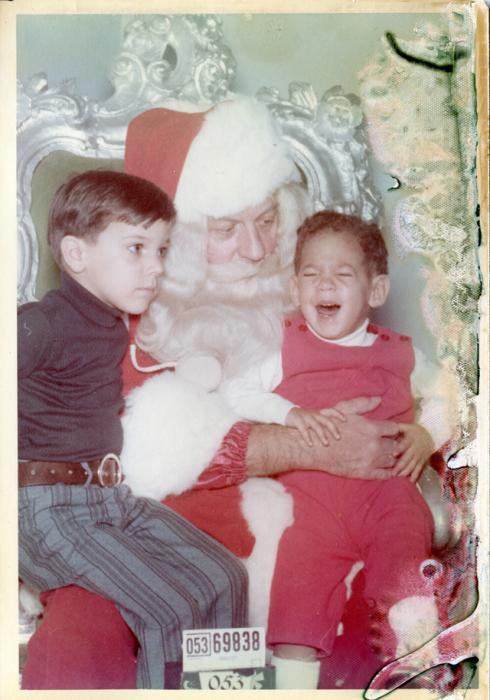 Санта-Клаус старается успокоить испугавшегося мальчика.