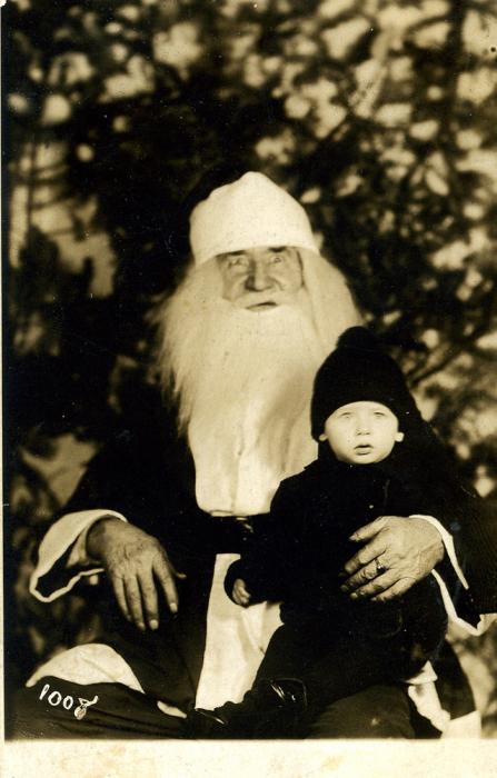 Толстый старичок с маленьким мальчиком на коленках позирует перед фотографом.