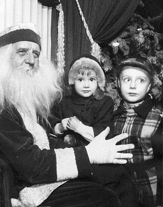Ребятишки и Санта-Клаус с огромным удовольствием делают снимок на память.