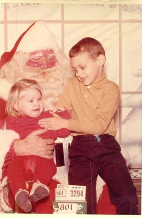 Старший брат успокаивает сестру, которая испугалась краснощекого деда.