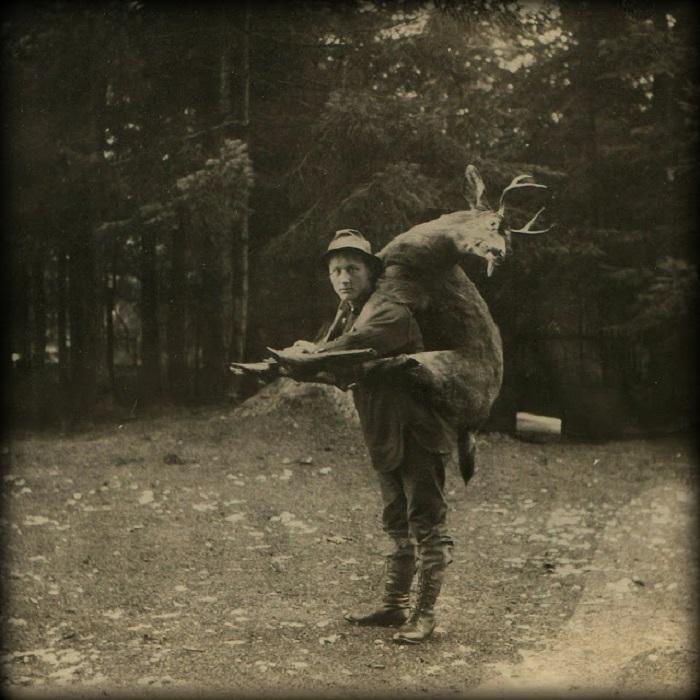Мужчина тащит оленя верхом на себе.