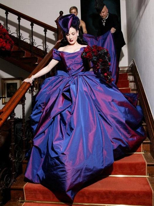 Восхитительная красавица со знаменитой осиной талией танцовщица спускается навстречу своему возлюбленному шок-рокеру в обворожительном платье от Vivienne Westwood.
