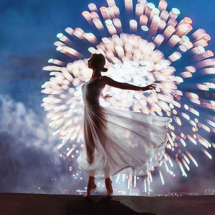 Изящная Нина в легком белом платье и ярких отблесках огней фестиваля фейерверков в Москве, Россия.