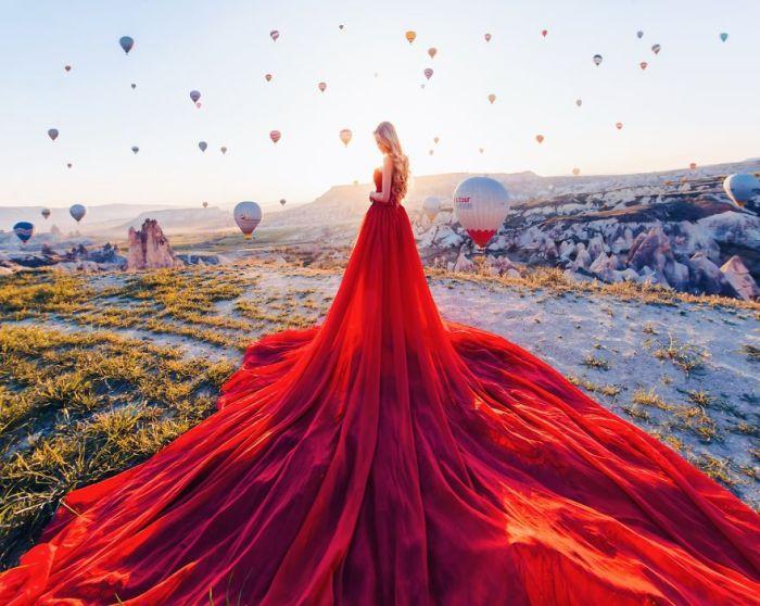 Белокурая Мария в роскошном красном платье на фоне неба и воздушных шаров в Каппадокии, Турция.