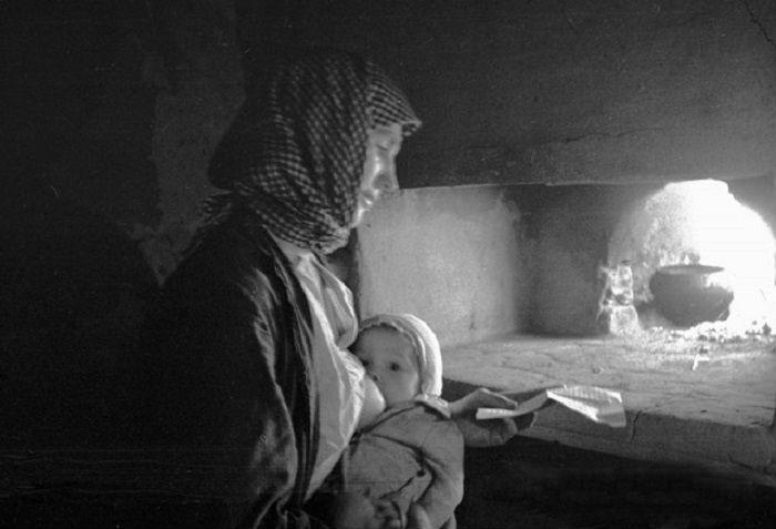 Женщина, кормящая грудью младенца, читает письмо с фронта.