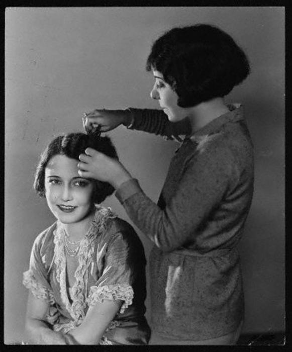 Девушки делают укладку волос, отделяя прядь от пряди.