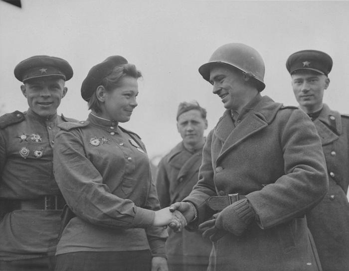 Советская военнослужащая пожимает руку американскому солдату.