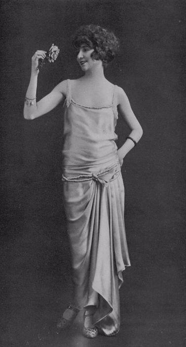 Девушка в льющемся наряде с браслетами и химической завивкой.