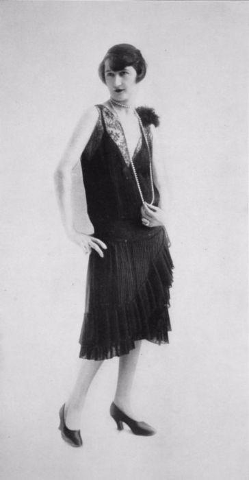 Плиссированное платье с мелкими рюшами и длинной ниткой жемчуга.
