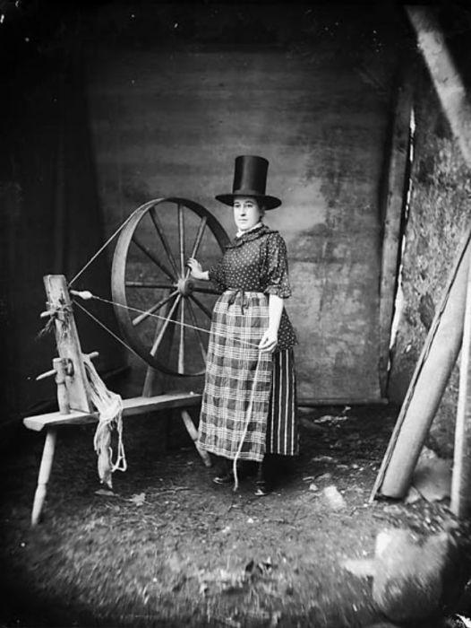 Женщина в национальном валлийском костюме и традиционной шляпе позирует у прялки фотографу Джону Томасу в 1885 году.