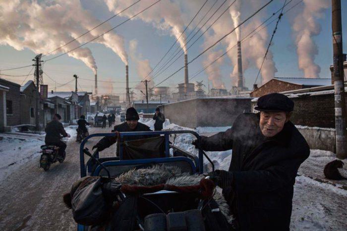 Китайские мужчины тащат телегу угля с местной электростанции, для отапливания своих домов.