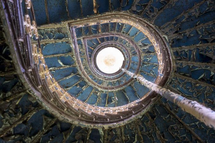 Спиральная лестница с голубой потрескавшейся краской в одном из опустевших польских дворцов.