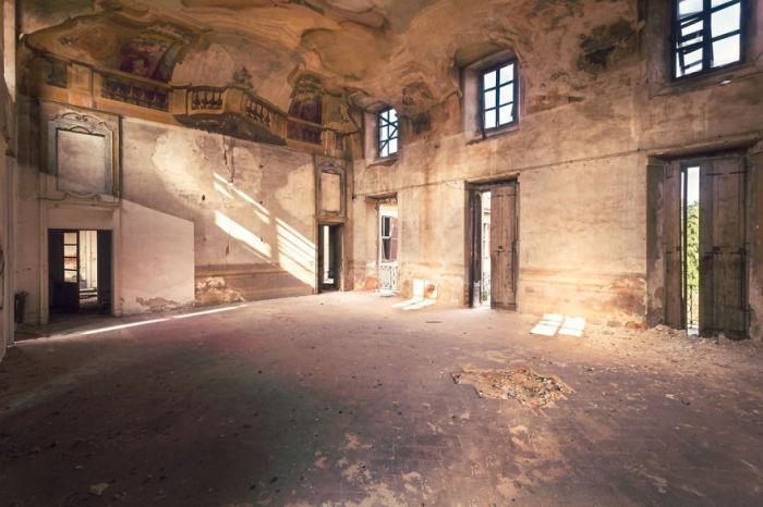 Главный зал покинутой итальянской виллы с реалистичными рисунками на потолке, которые сохранились после пожара.
