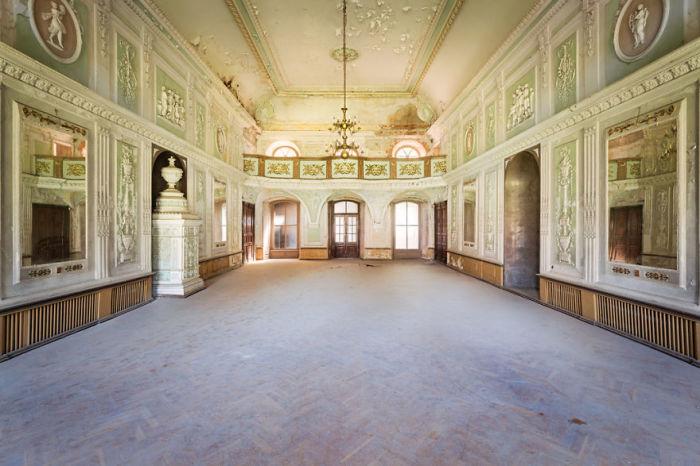 Бальный зал с паркетным полом, покрытым многолетней пылью, в одном из заброшенных польских дворцов 18-го века.