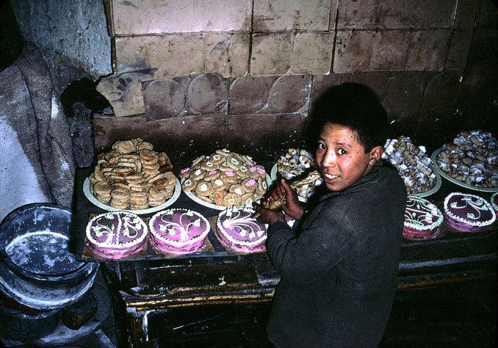 Афганский мальчик украшает торт.