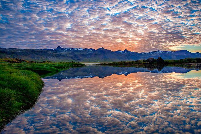 Облака отражаются в озере, как будто ватные хлопья разлетелись от дуновения ветра.