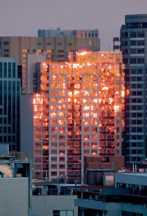 В конце дня, заходящее солнце огненными отблесками отражается в небоскребе.