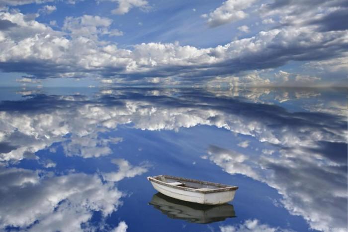 Лодка на прозрачной воде, в которой отражается небо.