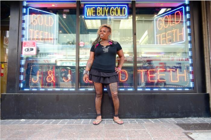 Девушка позирует перед витриной магазина.