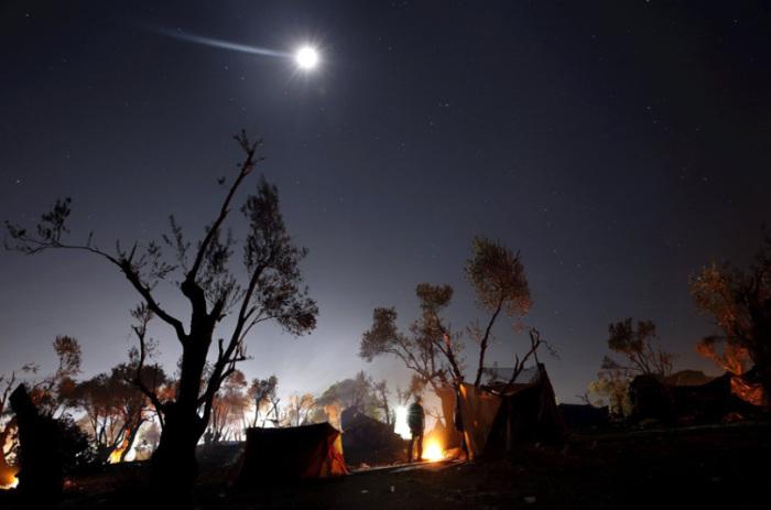 Беженец греется у костра в лагере недалеко от центра регистрации на острове Лесбос в Греции.