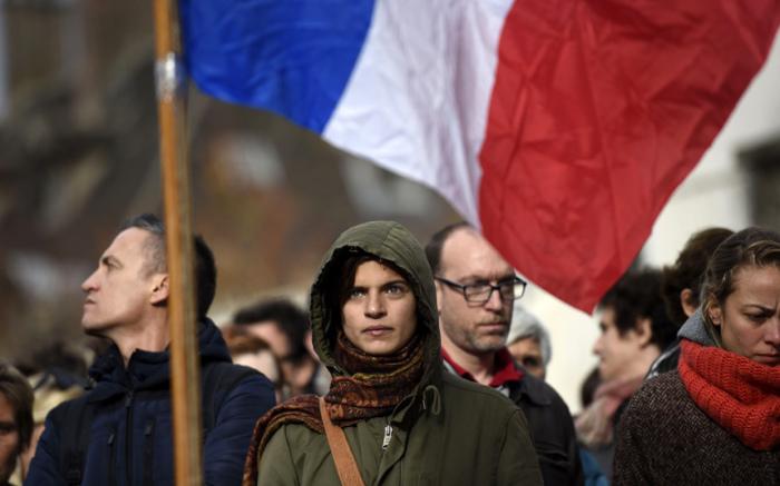 Люди соблюдают минуту молчания в память о жертвах терактов возле ресторана La Casa Nostra в Париже.