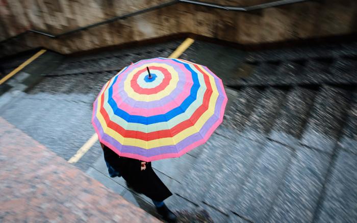 Яркий зонт привносит немного красок в пасмурный, дождливый день в центре Киева.