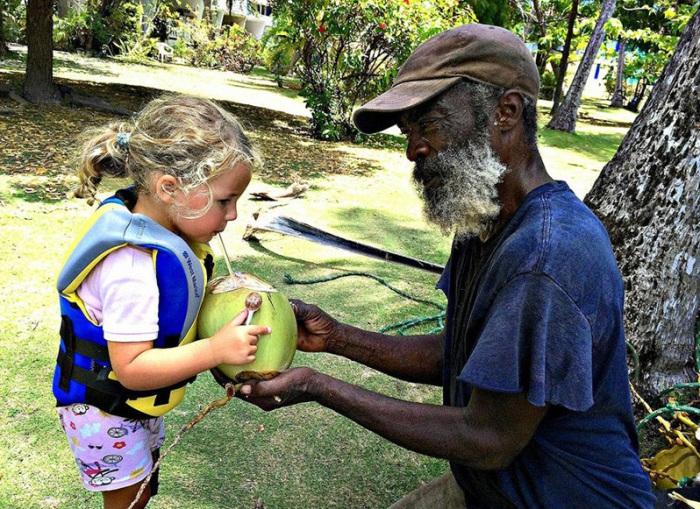 Мужчина взобрался на пальму, сорвал кокос, расколол его и дал Исле кокосовое молоко.