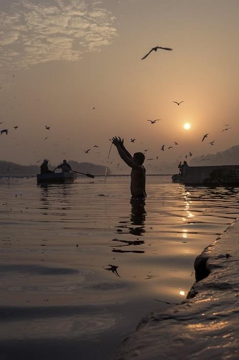 Верующий, который возносит молитву богу Солнца зимним утром у берега священной реки Джамна.