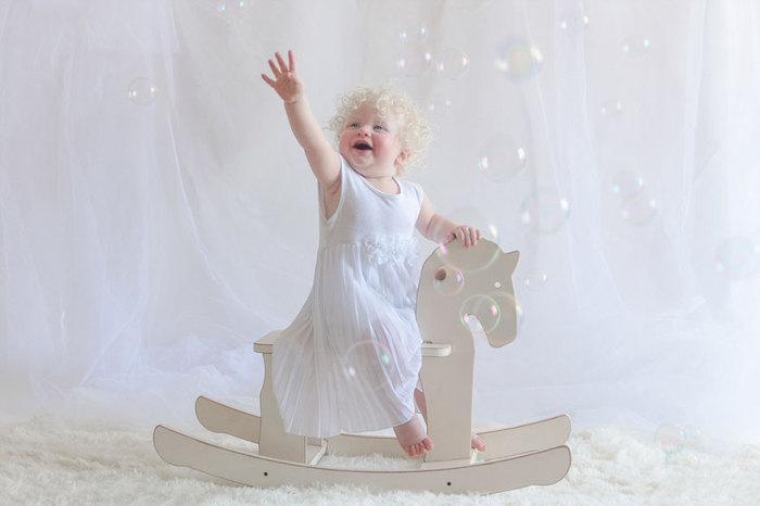 Мишель катается на деревянной лошадке, ловит мыльные пузыри и заливается смехом.