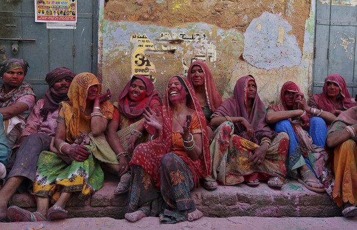 Индийские женщины, обсыпанные разноцветными красками, громко смеются, когда выполняется один из ритуалов празднества -  мужчин бьют бамбуковыми палками.