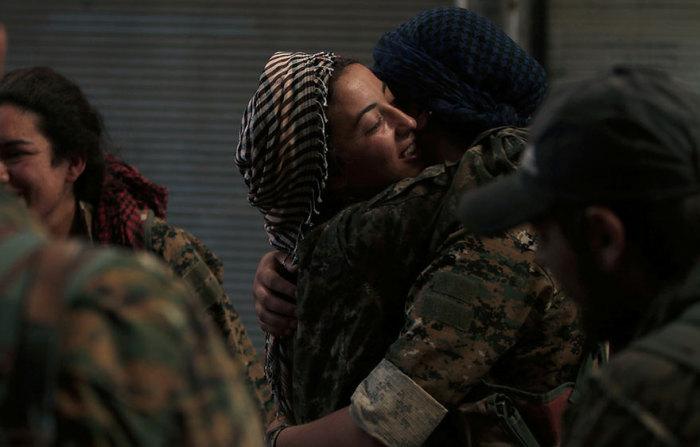 Сирийские военные бойцы обнимают друг друга в городе Манбидж в провинции Алеппо.
