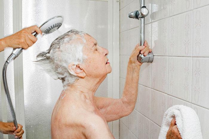 Дочка помогает маме принять душ, так как самостоятельно себя обслуживать пожилая женщина не может.