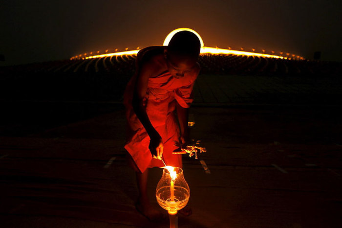 Буддийский монах зажигает свечу в храме на государственным праздником Маха Буча.
