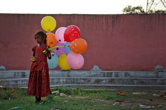 Девочка в национальном платье продает фрукты и шары на берегу реки Ямуна.