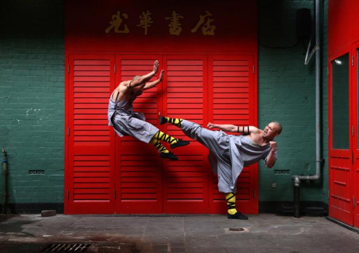 Шаолиньские монахи, владеющие кунг-фу, которое считается одним из древнейших видов боевых искусств, позируют фотографу во время визита в Великобританию.