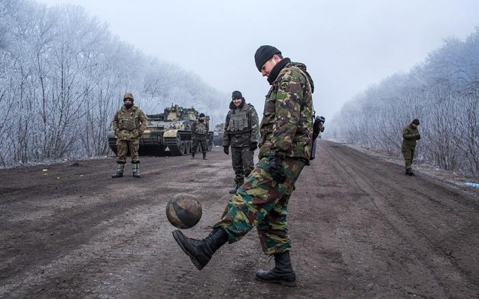 Бойцы ВСУ играют в футбол на дороге, ведущей в Дебальцево.