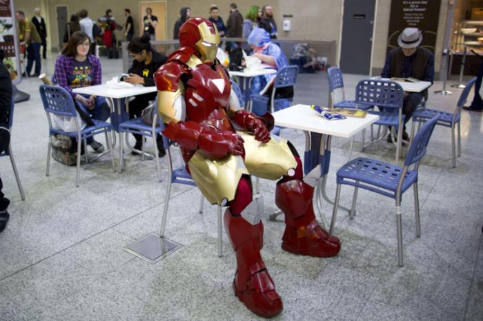 Мужчина в костюме Железного человека сидит в кафе на ежегодном съезде поклонников поп-культуры London Super ComicCon в Лондоне.
