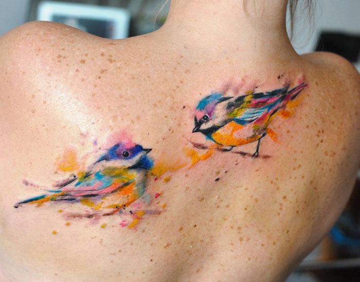 Татуировка пернатых друзей, сделанная в стиле акварель.