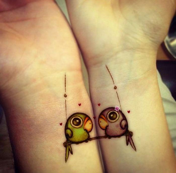 Руки влюбленных разрисованы одинаковыми изображениями.