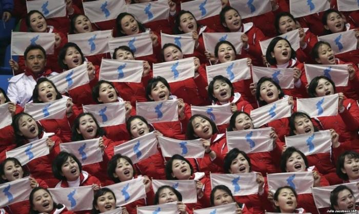 Северокорейские болельщицы держат в руках флаг объединенной Кореи, 10 февраля 2018 года.