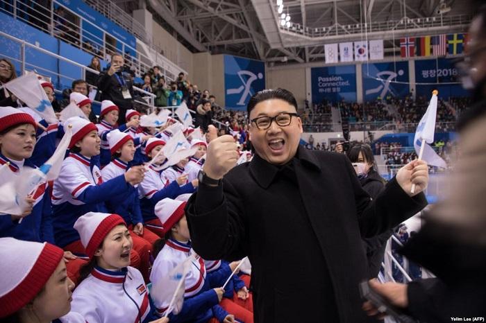 Двойник северокорейского лидера Ким Чен Ына, позирует на фоне болельщиц из КНДР.