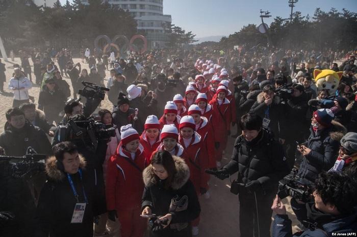 Журналисты окружили северокорейских болельщиц, которые прогуливаются по пляжу в Канныне.